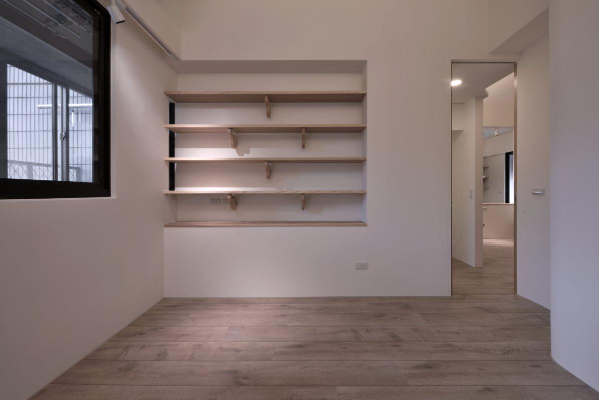 與廚房的雙向隔間櫃上半部是客房的書架,呼應客廳的主書牆