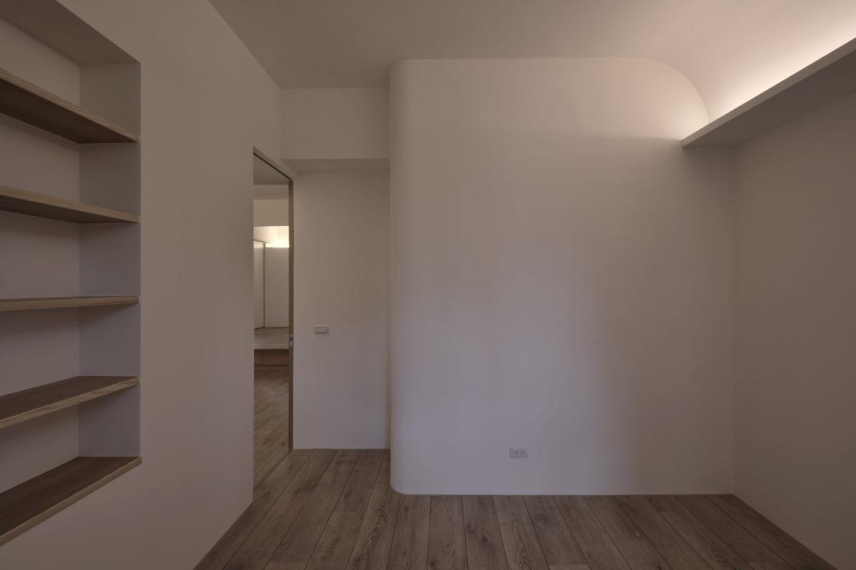 天花為了收樑角,呼應客房入口的圓弧一樣做了弧面處理,搭配間接光,柔和又簡約