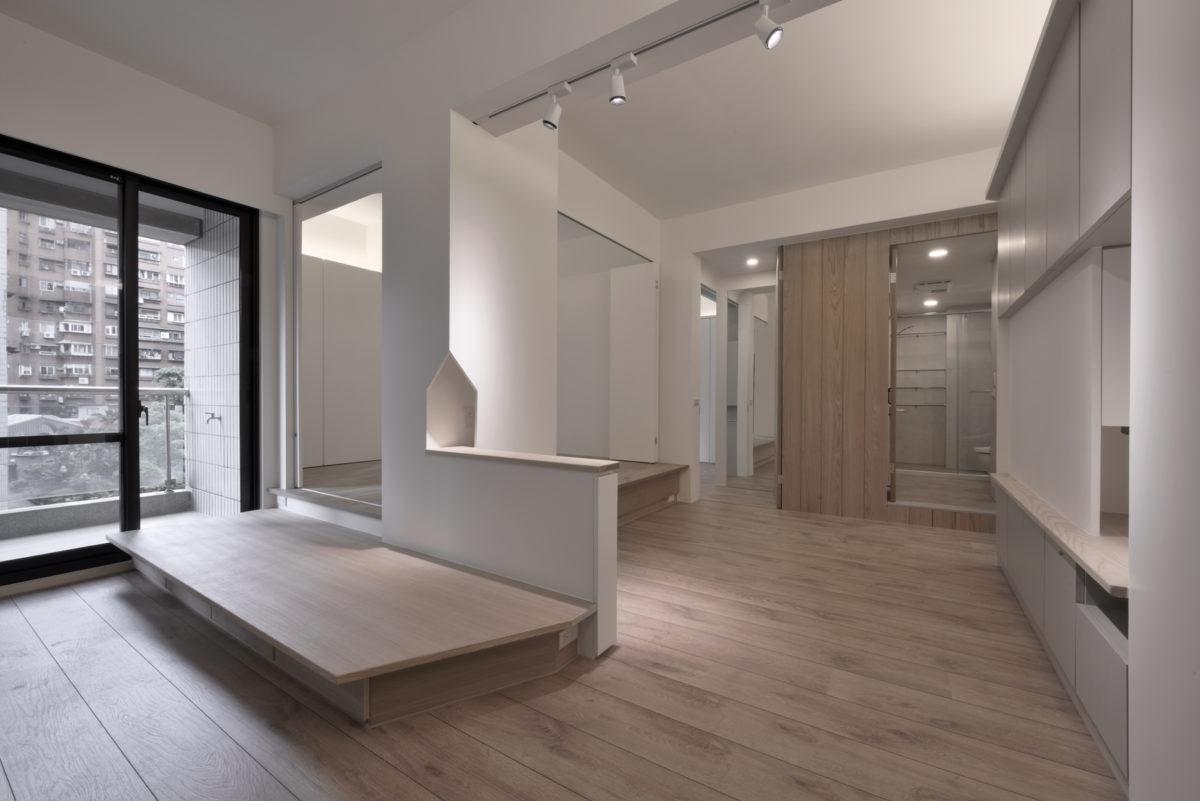 沈靜的白橡鋼刷木皮牆面,原來藏了三個門! 為了保持休憩平台與視聽區的空間完整性,將主臥門、客廁門與客房門做成自動回歸的隱藏門,這樣既保有動線的方便又不影響空間感