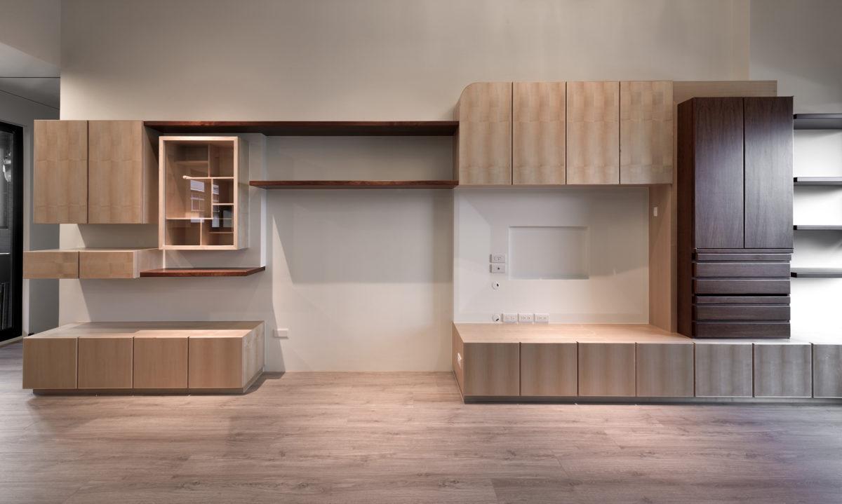 餐客廳面對的主書牆是此案的重點設計之一,因為有展示與祖先櫃的需求,祖先櫃也有指定的位置與幾個必須符合的尺寸,在設計上我希望既要滿足業主提出的「活潑大方不複雜」,又希望在整體和諧的前提下,帶出祖先櫃的莊嚴優雅與展示櫃的畫龍點睛,因此產生了這個立面。 在思考材料搭配時,因為業主有提出希望不同木皮混搭,在本工作室蔡芳琪 設計師的建議下,我們嘗試了以舒坦感的極淺灰牆做底,楓木為主調,搭配花梨木的水平層板與祖先櫃的組合,才最終定出空間的主調。