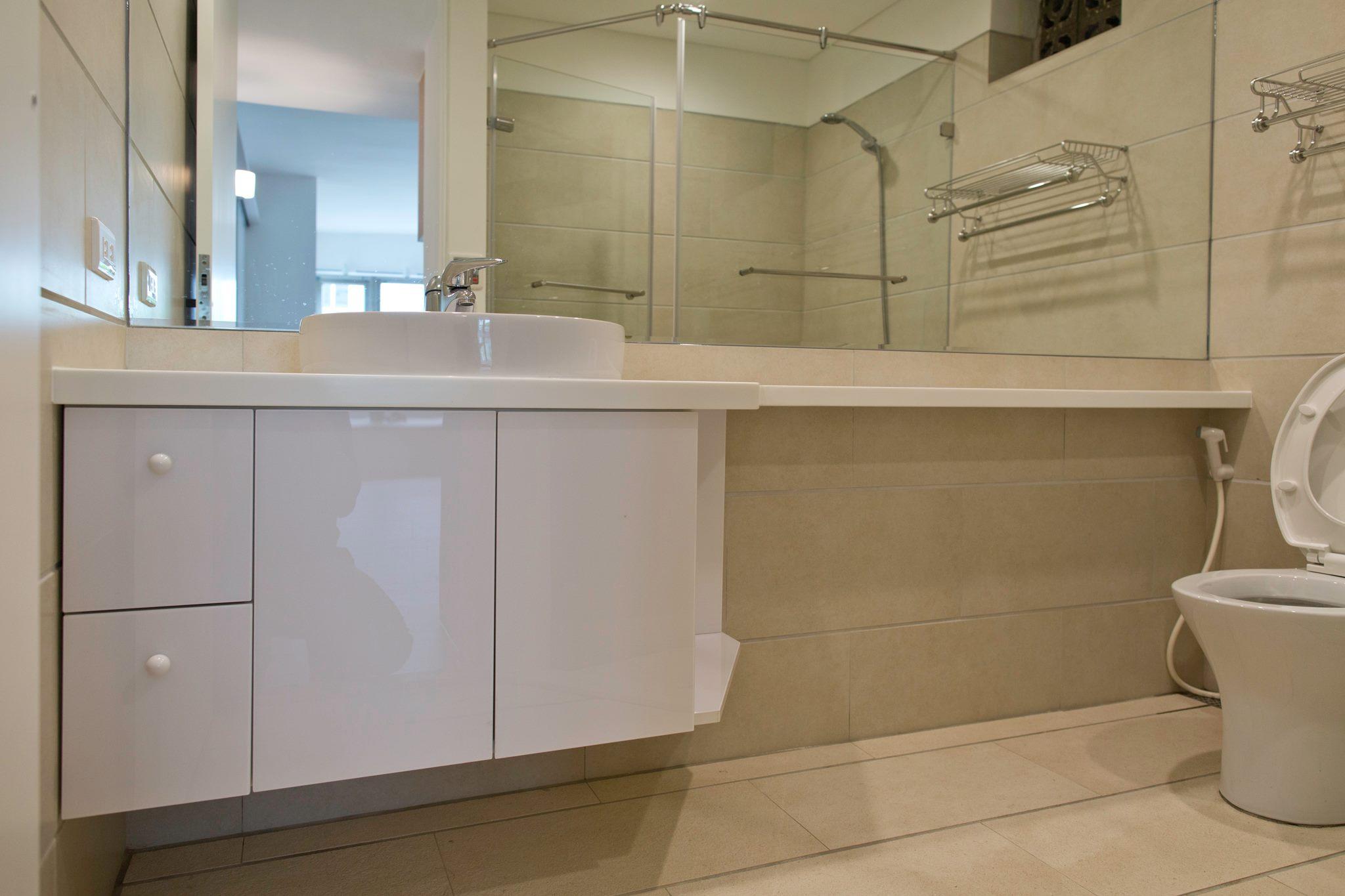 浴櫃檯面一直延伸到馬桶邊,方便置物。正面的鏡子對於小廁所的空間感有很大的幫助