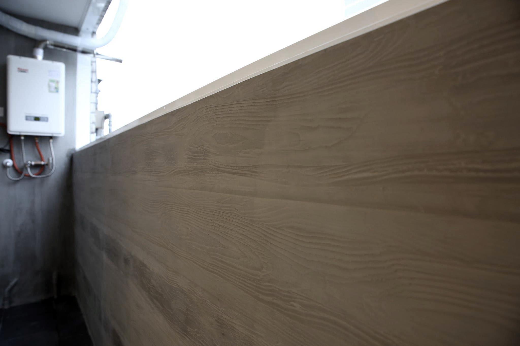 後陽台的牆面採用木紋水泥面,簡單呼應室內氛圍