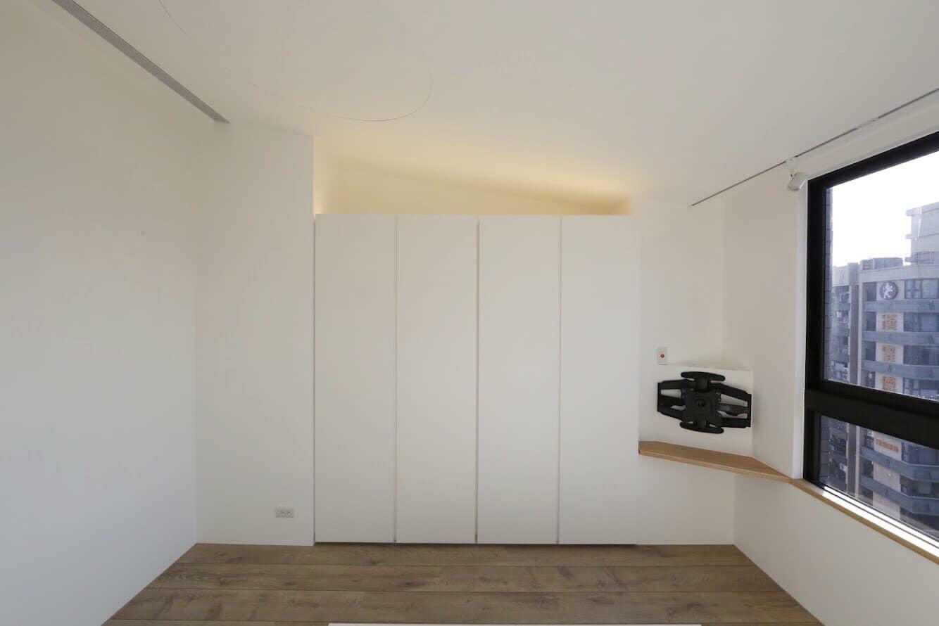 主臥與客廳天花的斜度反向,是希望收束精神,臥室是需要休息的空間,適度的安全包覆是必要的。 天花上圓型維修孔既可讓吊隱式冷氣在必要時整台卸下維修,又能呼應消防灑水頭與感知器的圓,貫徹設計的完整性,ㄧ舉數得。