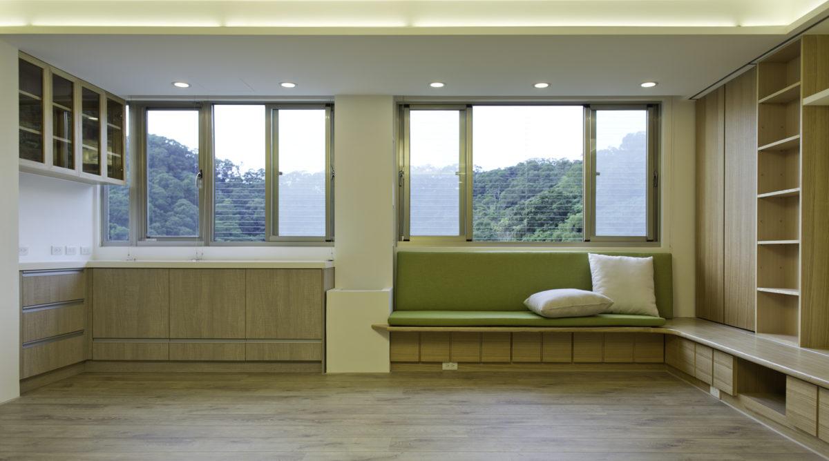 窗邊的平台加上座墊,代替了沙發的功能,而它的下方也都是整排的抽屜。左邊的白色花台則是要讓業主種植植栽。整排的序列窗戶有良好的採光,並可以看到旁邊美麗的山景。