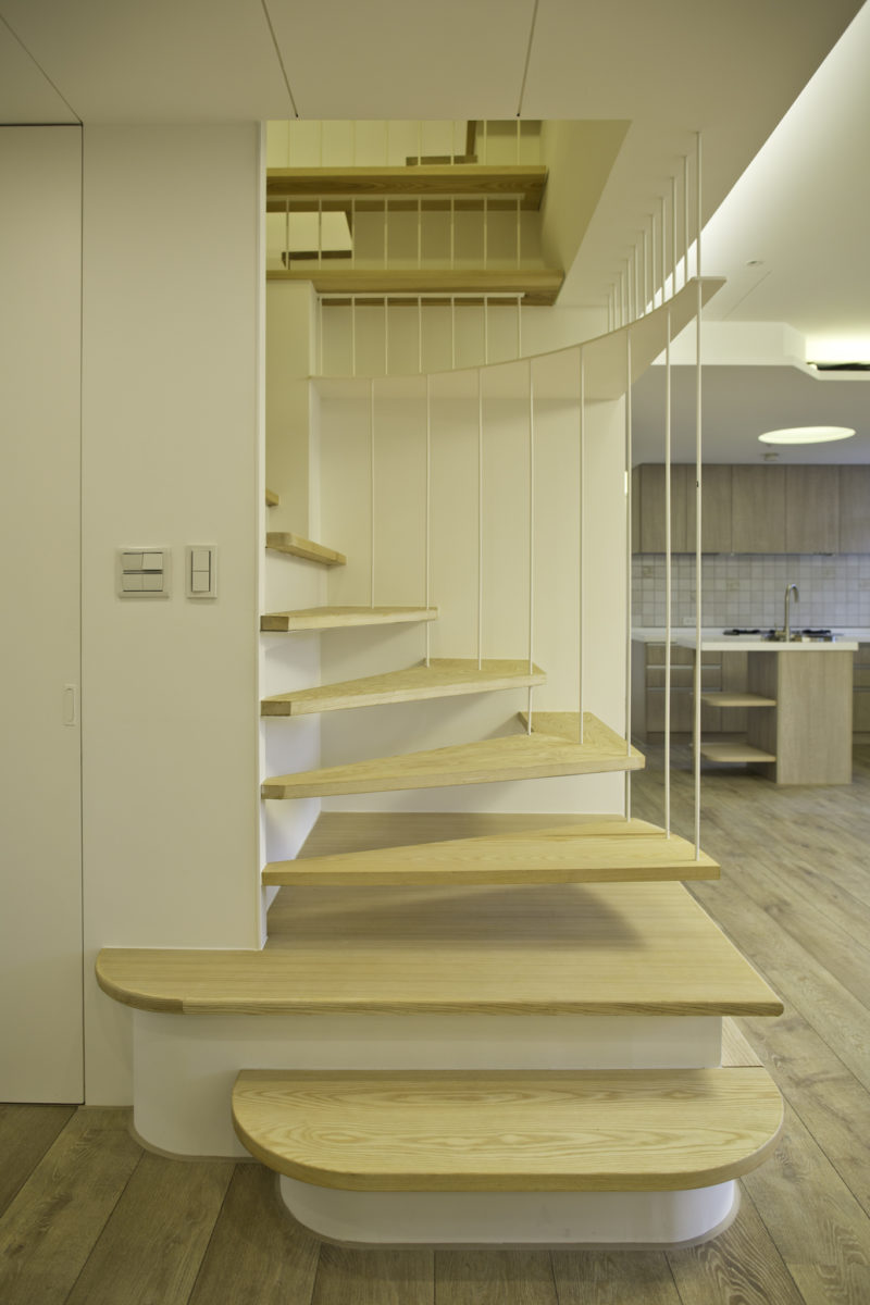 考量有四階踏階是需要鐵件懸吊以強化結構,加上業主擔心樓梯井如果只有腰高的欄杆還是有兒童安全上的顧慮,因此在設計上,我們決定採用格柵鐵件,結合防墜網與懸吊結構的需求,成為此樓梯設計的一個特色。 搭配適當的踏階延伸成上下樓梯之間的層板系統,可作扶手又可置物,一舉數得。