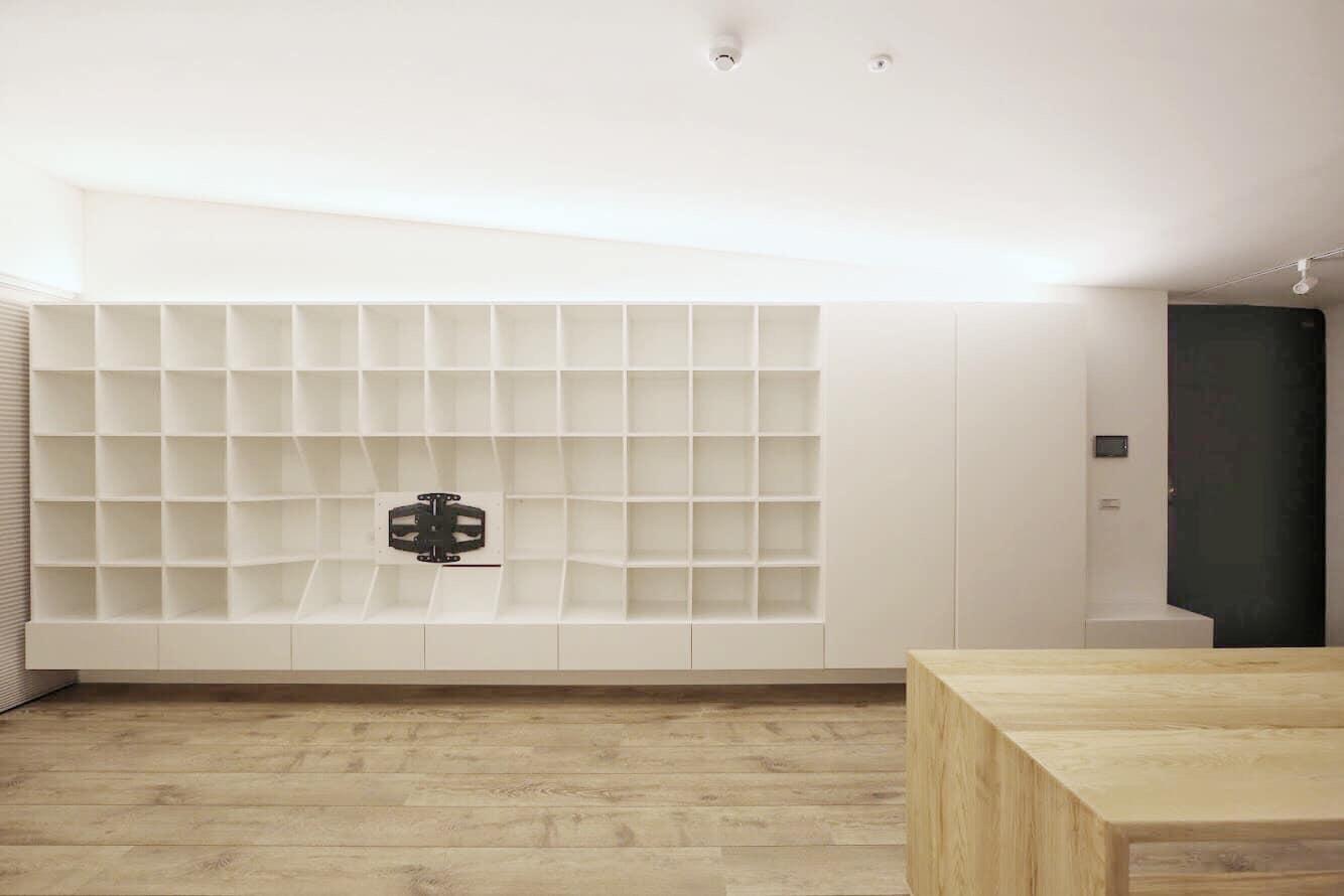 整個公共區域以整面的收納造型櫃搭配斜面天花做爲主牆,從入口的穿鞋平台抽屜、衣帽鞋櫃到整面結合電視的格子架,盡量滿足小空間的收納需求。 格子的尺寸參考IKEA的置物格大小,讓業主能輕鬆搭配需要的收納格。 斜面天花收掉入口處的深樑,強調「迎向窗」的開闊感,並整合後方三個門片成爲ㄧ氣呵成的設計,讓整個空間不受到出入口的切割,維持了整體性。