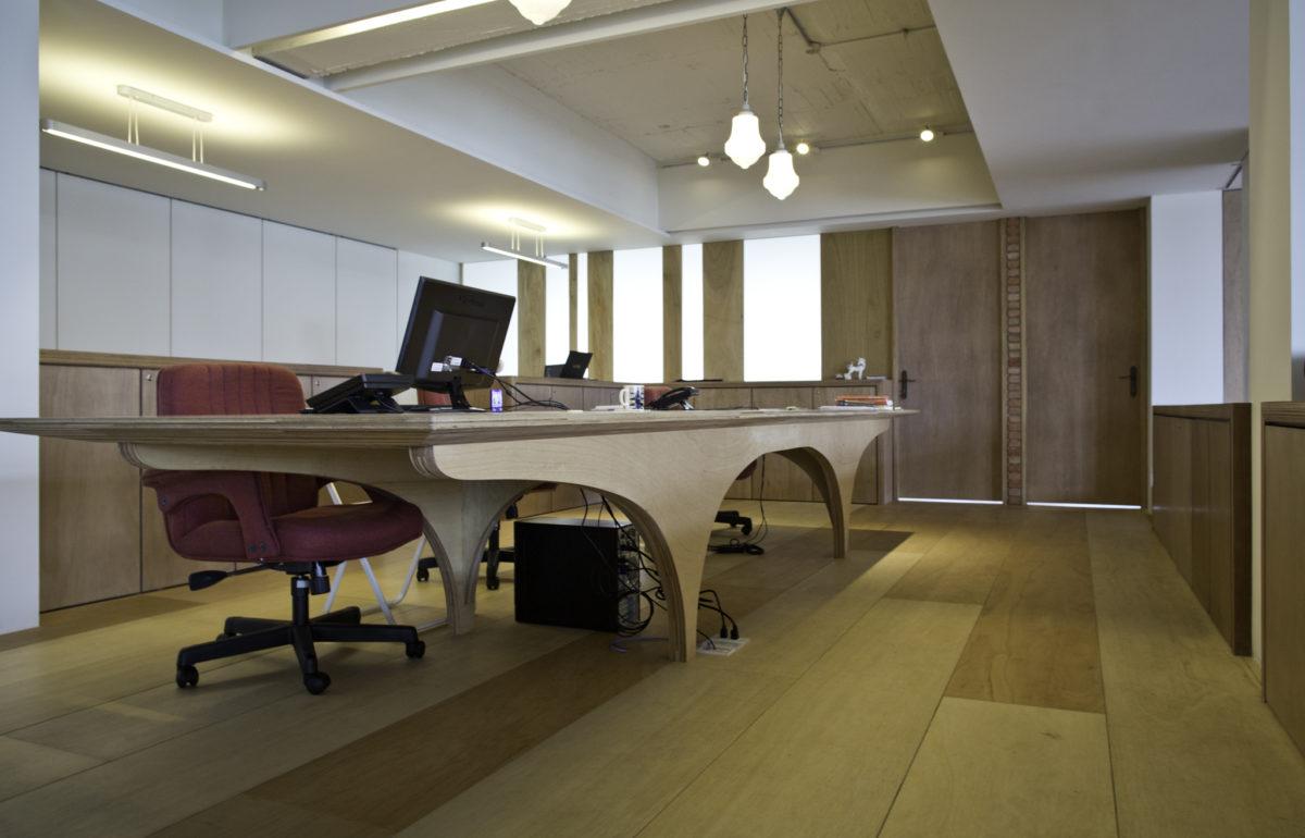 為辦公區設計的辦公大桌!在本設計案中,從木作隔件、書架、各式辦 公桌、廁所隔屏到木地板,都是使用夾板作為主材料,依照夾板特性設 計,木工現場製作完成的