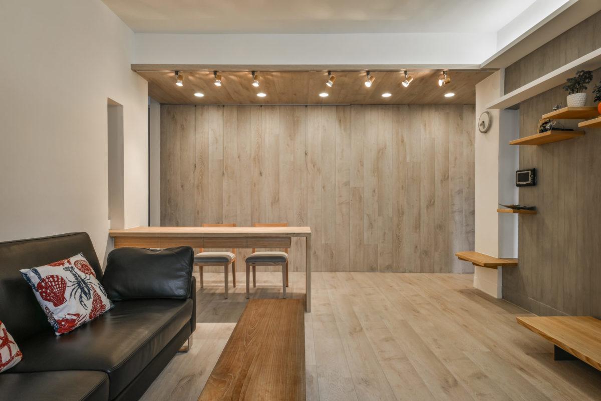 由於此案空間不大,因此利用木牆將兩個房間門完全隱藏起來,平常便可以保有客餐廳的空間完整性