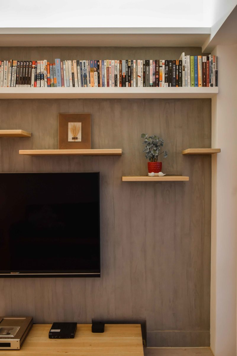 因為業主有養貓,客廳主牆層板以貓跳板發想,搭配木紋清水模質感的牆面,雅致中帶有活力